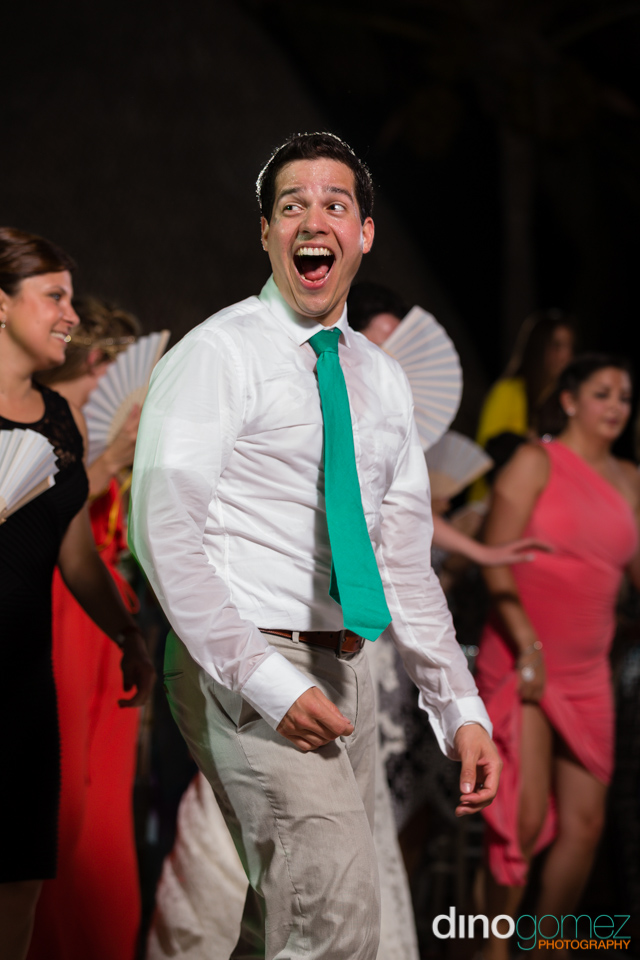Groom in green tie laughing in Los Cabos Mexico