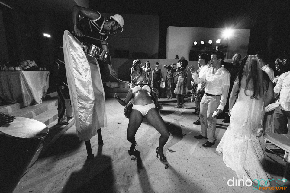 A black and white snap of a female performer doing the limbo at a destination wedding