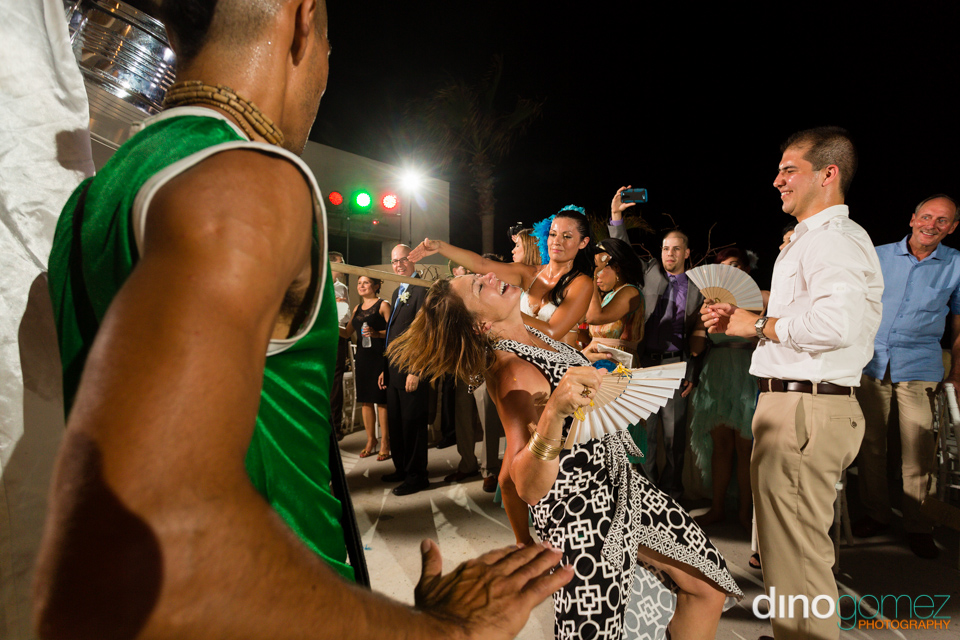 A very well dressed lady doing the limbo at a destination wedding in Los Cabos