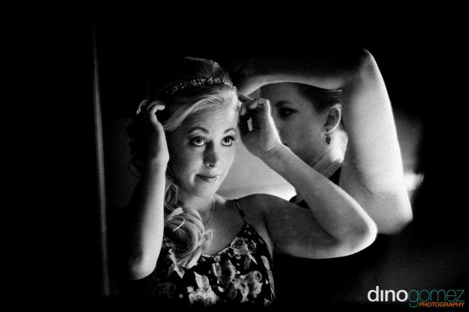 A black and white portrait of a beautiful bride fixing her hair taken by Dino Gomez