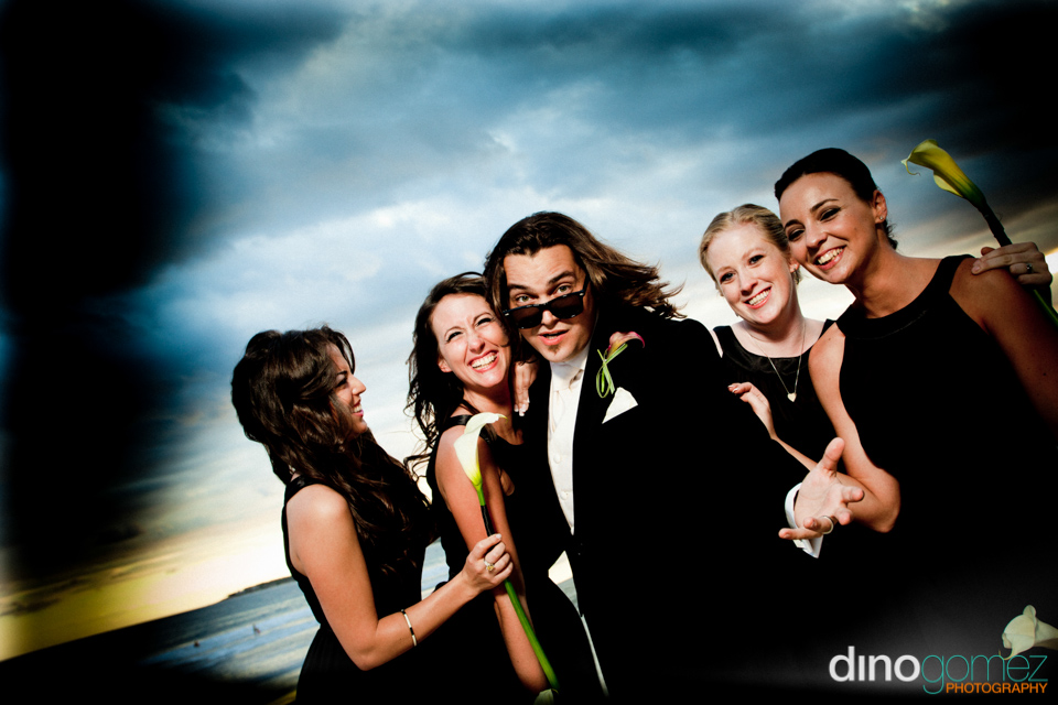 A casual photgraph of the groom and four beautiful bridesmaids on the beach during his destination wedding.