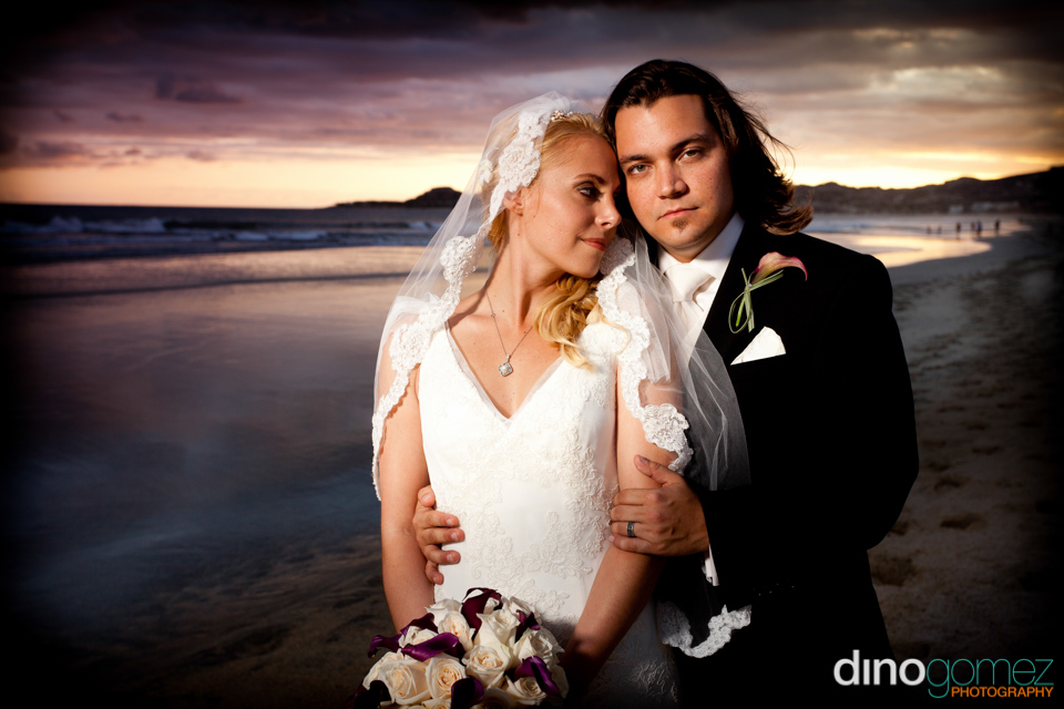 Destination Wedding photograph on a beach with two newlyweds embracing