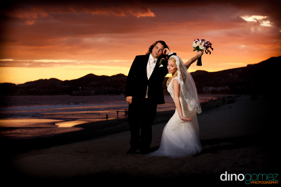 Newlyweds casually pose on the cabo san lucas beach at sunset