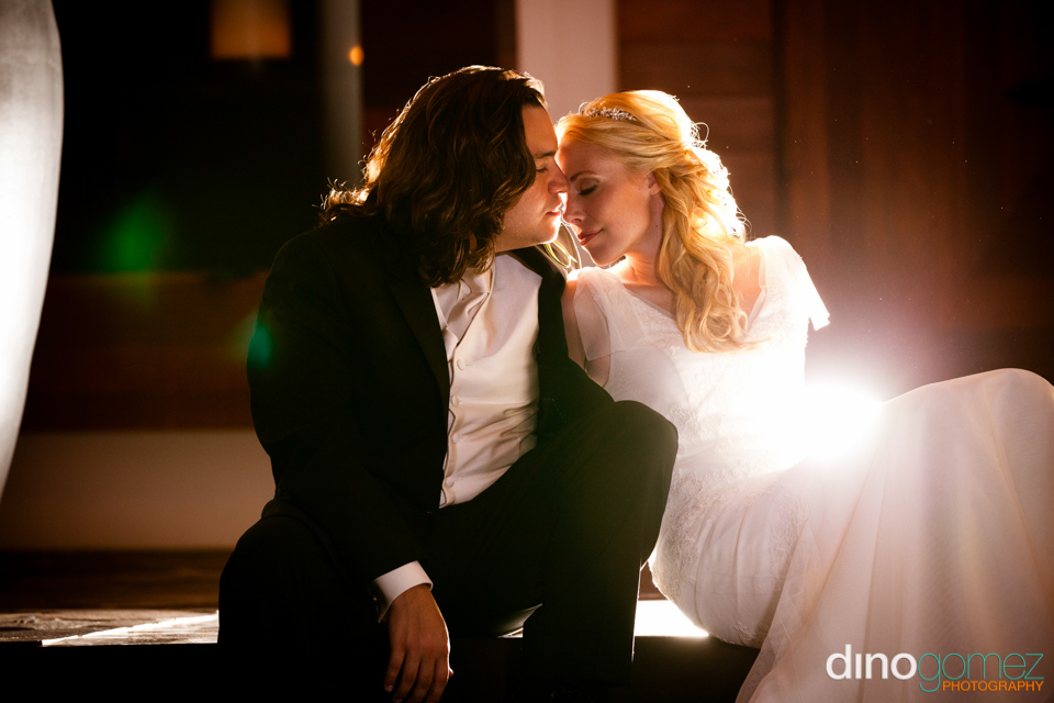 An artistic wedding photograph showing a tender moment between two newlyweds