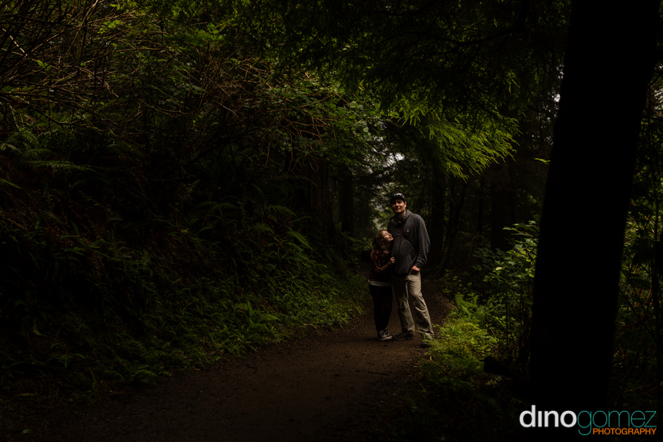 Father hugging his daughter on a path in the forest in Portland, OR