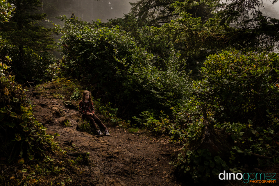 Lovely and charming shot of a girl sitting on a rock with some lush shrubs behind her in Portland, OR