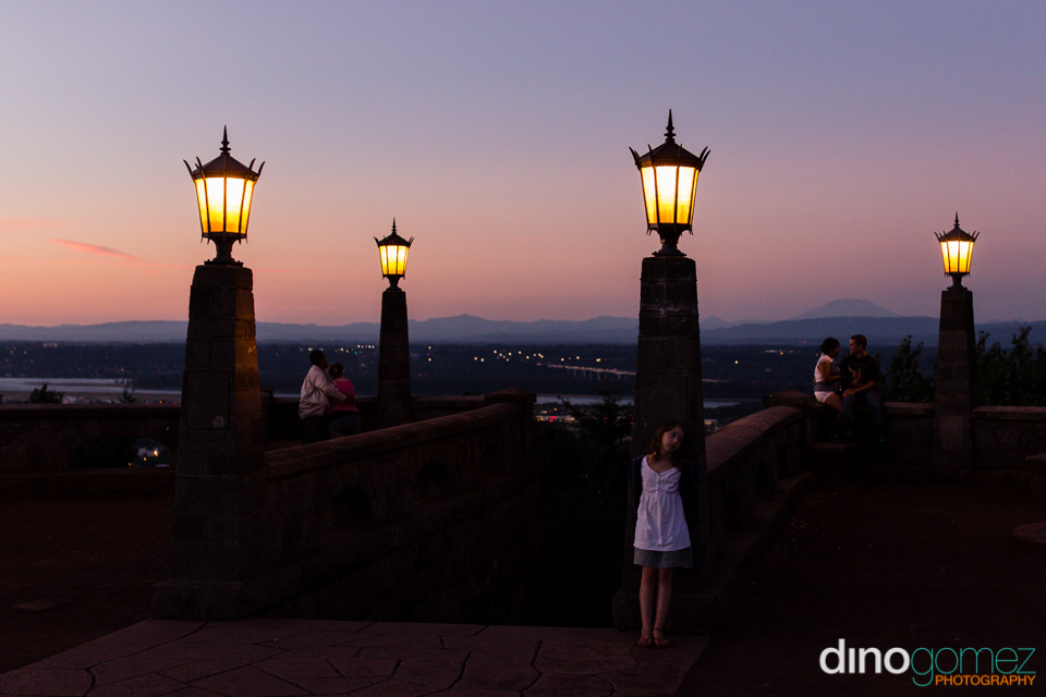 Amazing view of a girl leaning on a column with the skyline behind her from photographer Dino Gomez