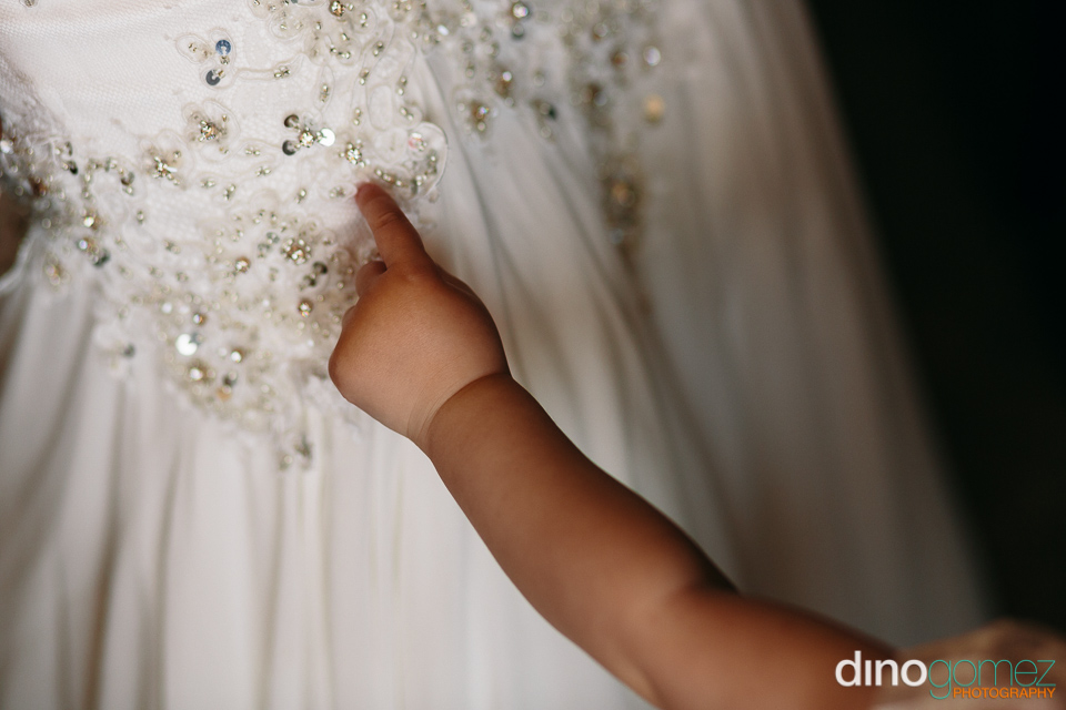 Baby pointing on the wedding dress details