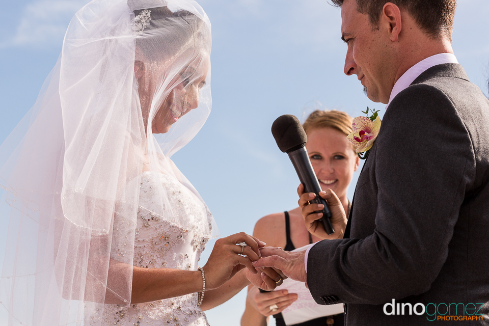Bride putting ring on the groom's finger during the destination wedding ceremony in Mexico