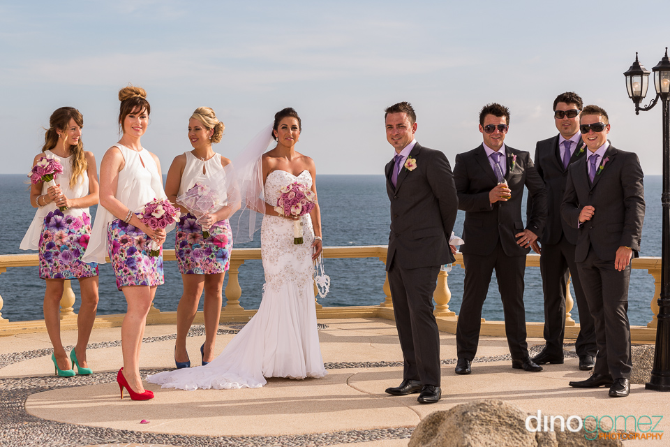 Newlyweds and the bridal party standing on a deck with the ocean in the background