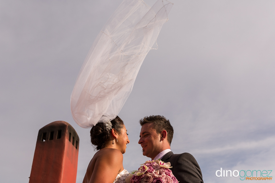 Bride's veil flying in the air as she looks and smile at her groom