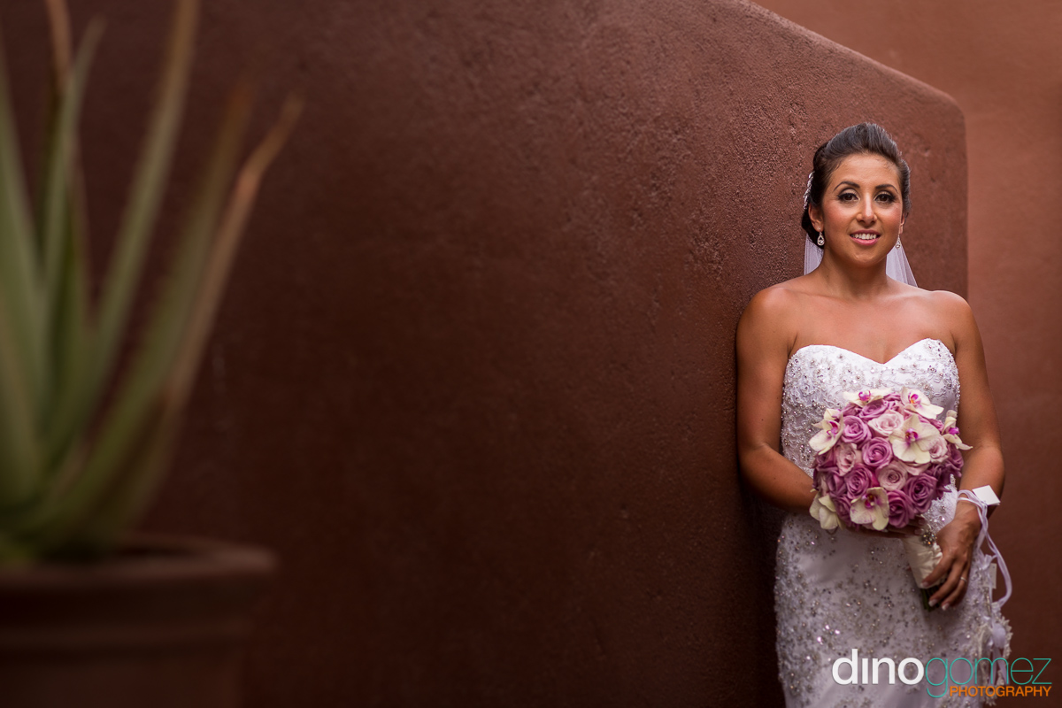 Bride with her wedding bouquet leaning against the wall in Mexico