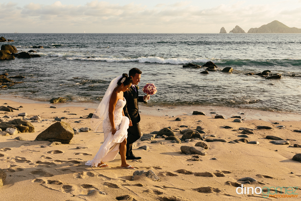 Beautiful side shot of the bride and groom walking on the beach by destination wedding photographer Dino Gomez