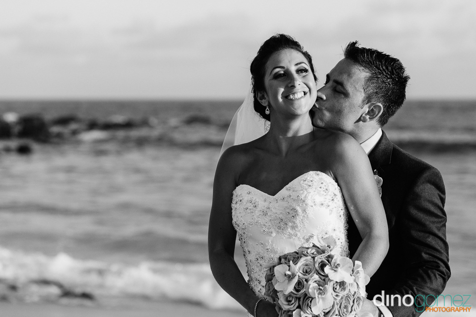 Black and white shot of the groom kissing his bride's neck on the beach