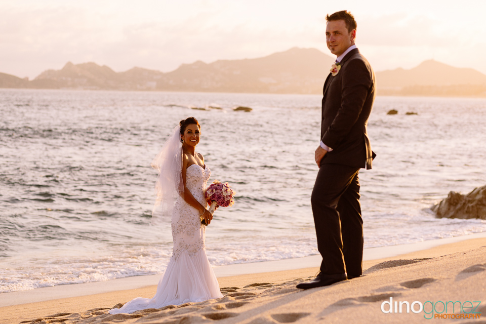 Newlyweds standing a short distance away from each other on the beach in Los Cabos Mexico