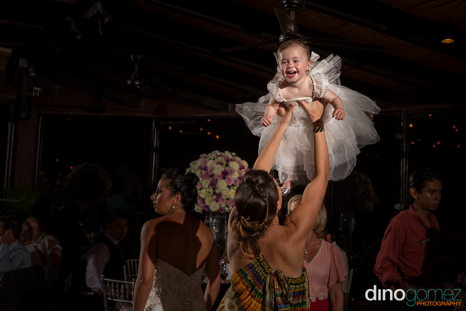 Beautiful little girl smiling as she is held in the air by a lady at the wedding reception