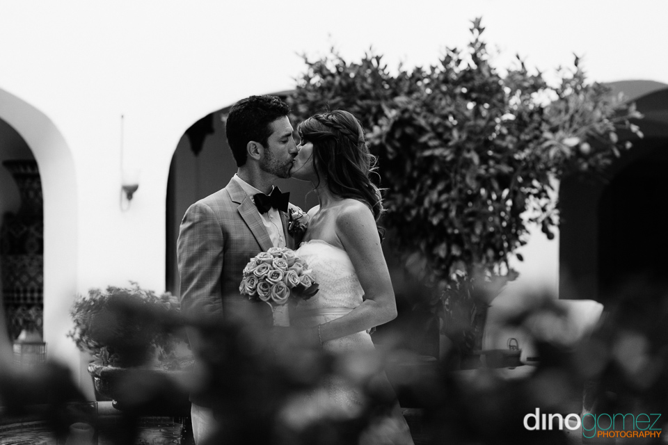 A Classic Black And White Photo Of The Newlyweds Kissing Outside In Los Cabos