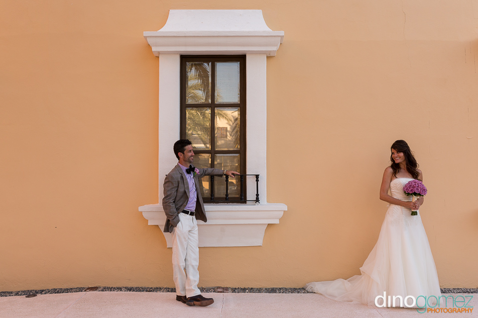 A Handsome Groom Leaning On A Window And Smiling At His Bride In Mexico