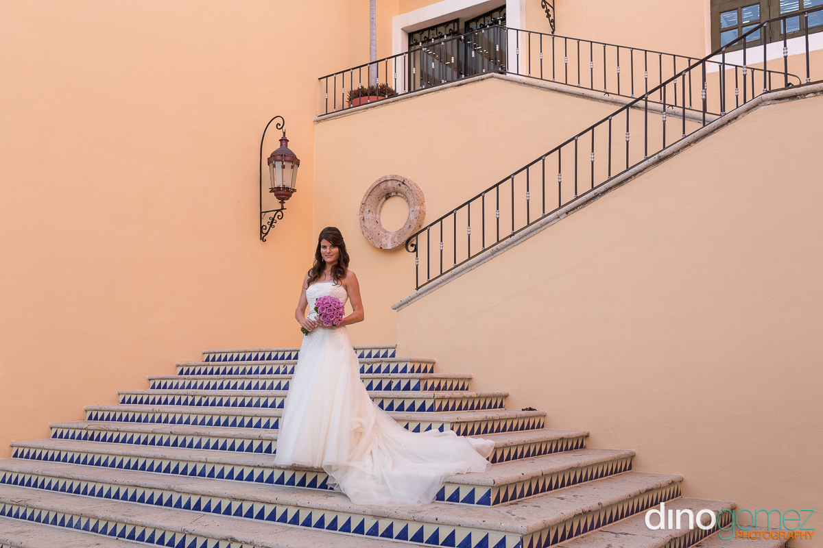 Beautiful shot of a bride on the stairs by the talented destination wedding photographer in Cabo Dino Gomez