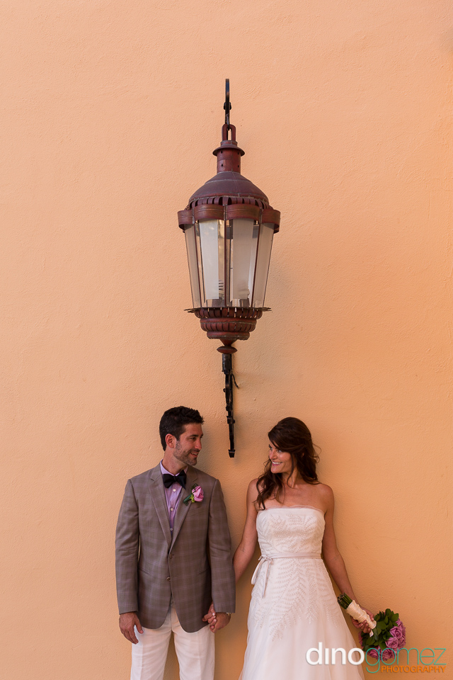 Destination Jewish Wedding Couple Leaning Against Wall And Holding Hands In Mexico