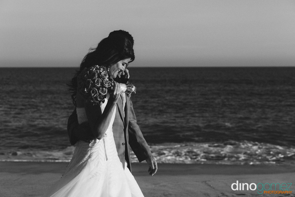 Gorgeous Couple Walking On The Beach As Photographed By Destination Wedding Photographer Dino Gomez