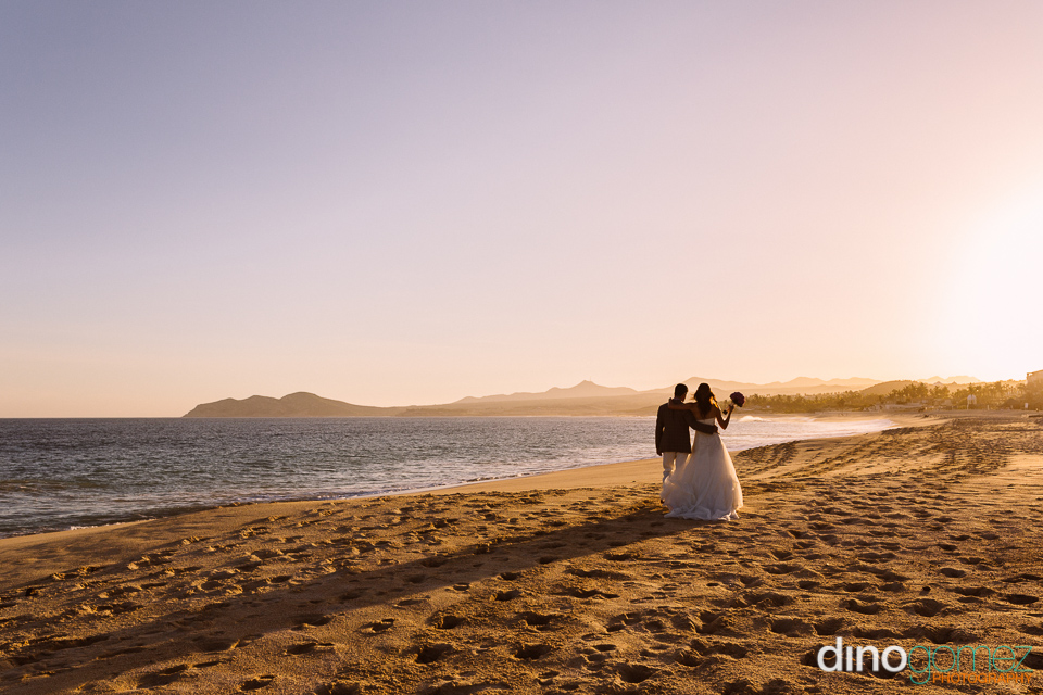 Couple Walking On The Beach At Sunset By Photographer Dino Gomez