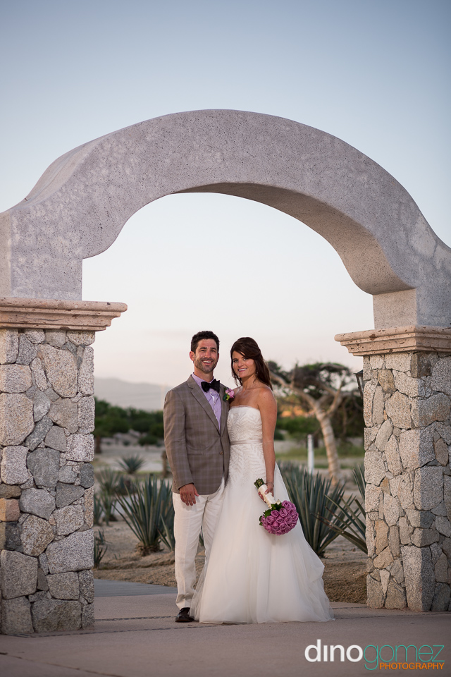 Destination wedding bride and groom underneath a stone arch in Los Cabos