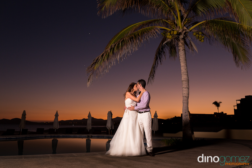 Wedding Couple Kissing At Sunset Next To The Pool And A Coconut Tree