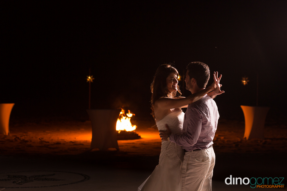A Shot Of The Bride And Groom Dancing And Smiling With A Fire Burning In The Background By Destination Wedding Photographer Dino Gomez