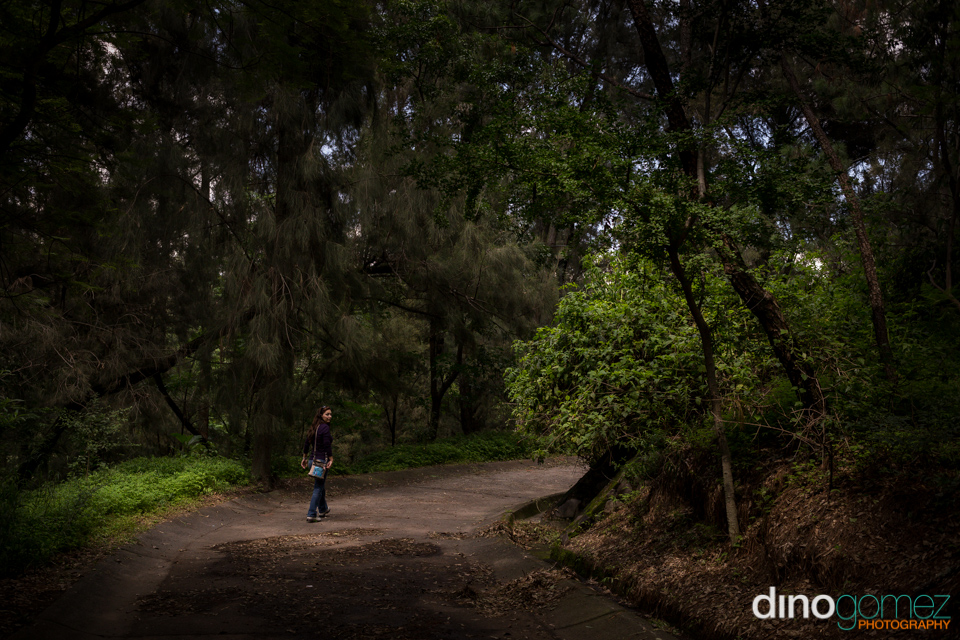 Young woman walking alone outdoors under tree in Guadalajara
