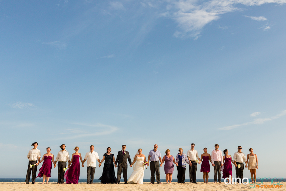 Wedding guests on the beach holding hands with the bride and groom