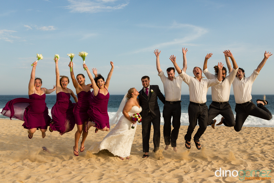Super cute wedding party pose on the beach by photographer Dino Gomez