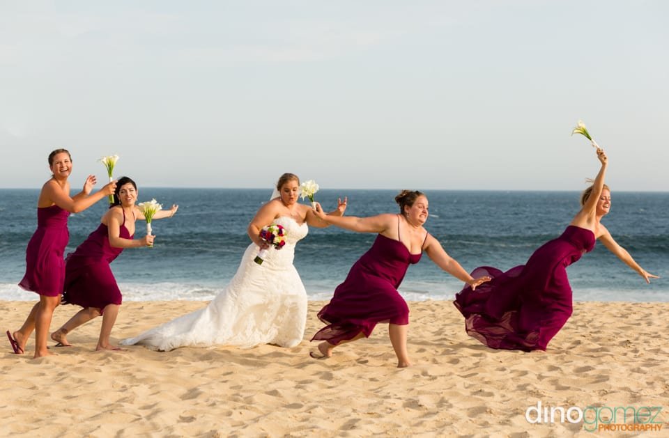 A fun shot of the bride and bridesmaids on the beach in Los Cabos Mexico