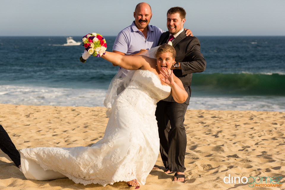 Fun pose with the bride and groom on the beach in Los Cabos with wedding photographer Dino Gomez