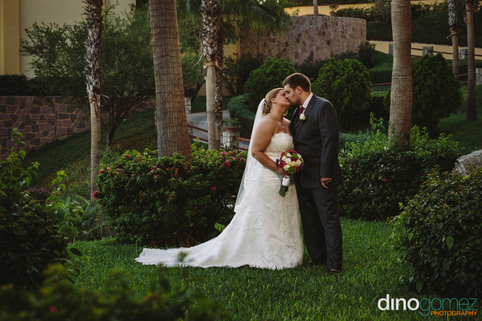 Bride and groom kissing in the garden after the wedding ceremony in Mexico