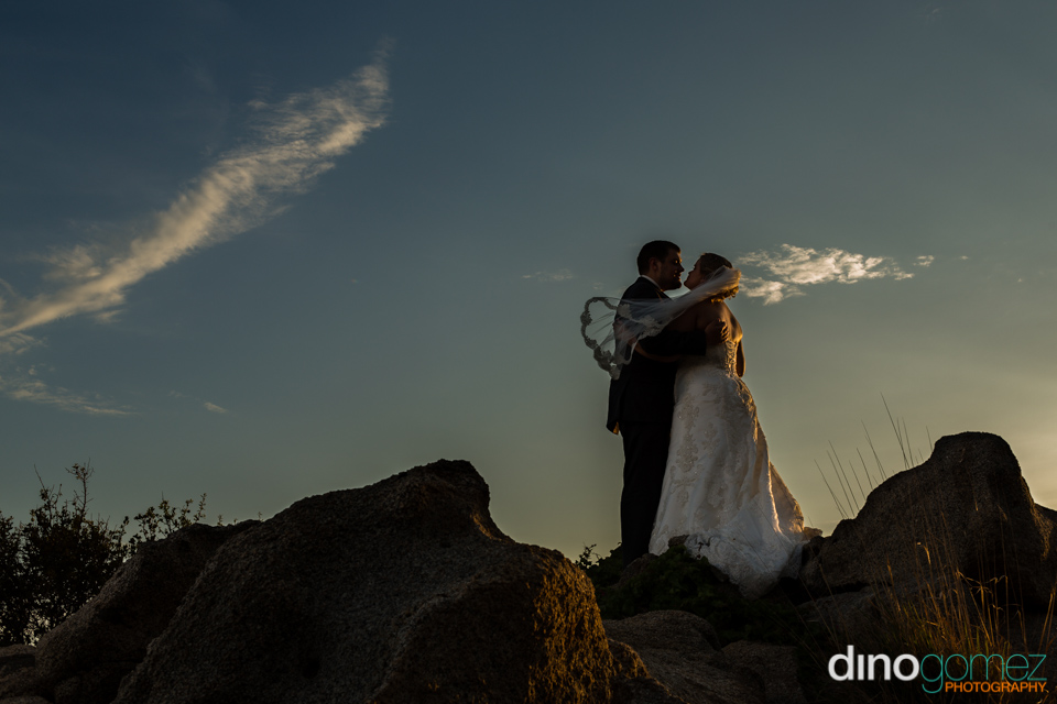 Beautiful shot of the bride and groom standing on the rocks at sunset by destination wedding photographer Dino Gomez