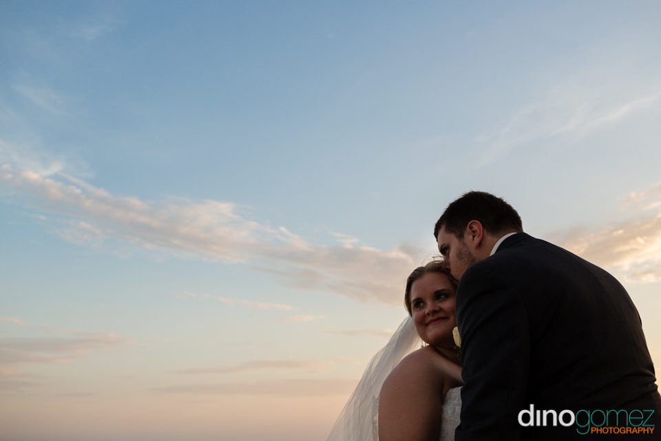 Beautiful shot of the affectionate peek on the side of the bride's head by the groom by wedding photographer Dino Gomez