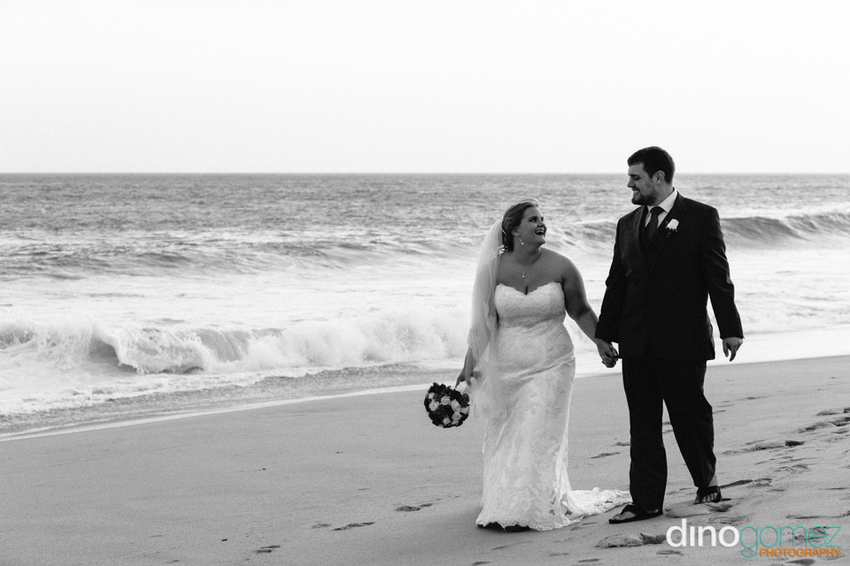 Wedding shot of the newlywed couple holding hands while walking on beach by destination wedding photographer Dino Gomez