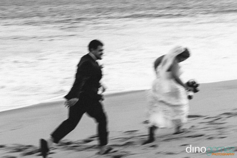 A cool shot in black and white of the groom chasing the bride down the beach by wedding photographer in Cabo Dino Gomez