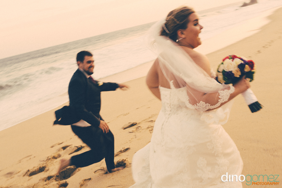 Newlyweds sharing a romantic and fun moment at the beach as captured by wedding photographer Dino Gomez
