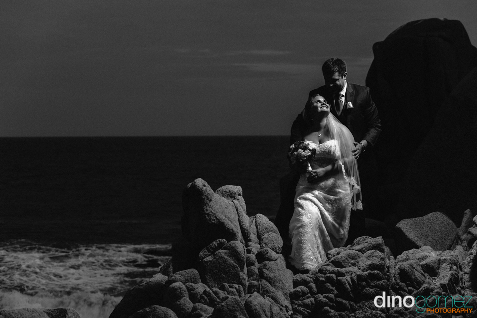 Gorgeous shot of the bride and groom standing on the rocks in Mexico