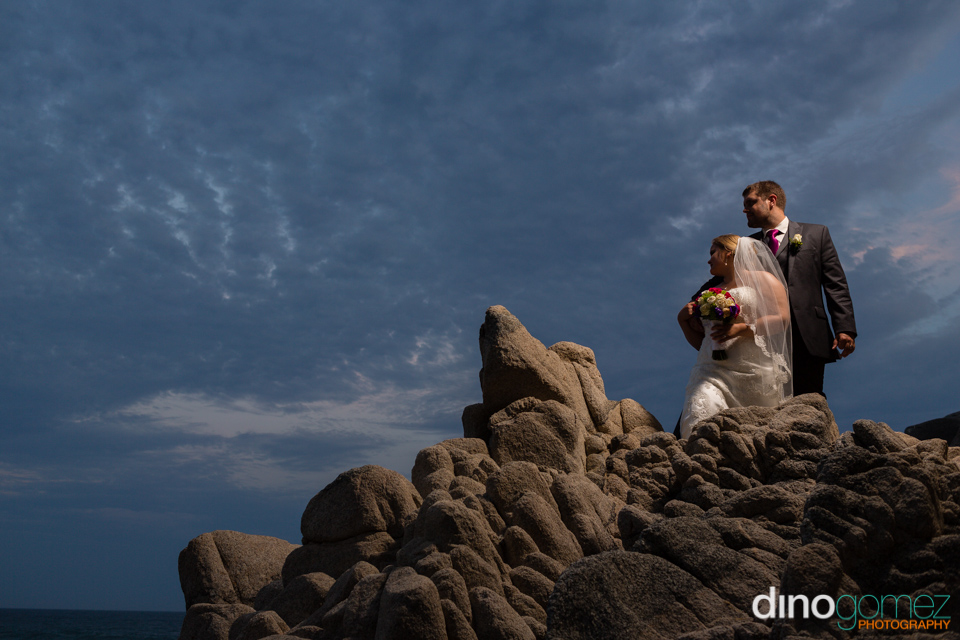 Newlyweds standing on the rocks overlooking the ocean in Mexico