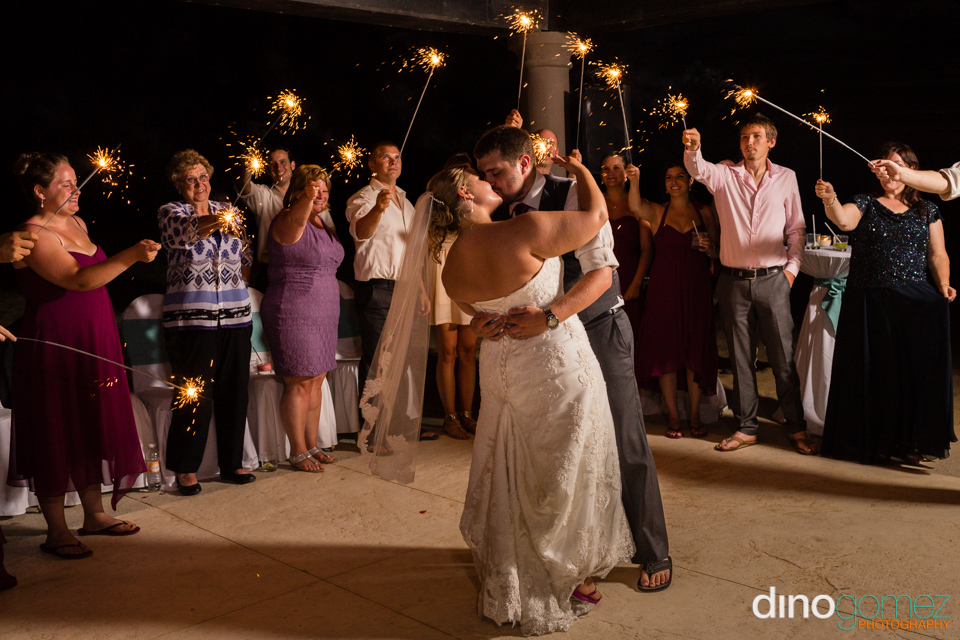 Newlyweds kissing in a circle made of sparklers in Mexico