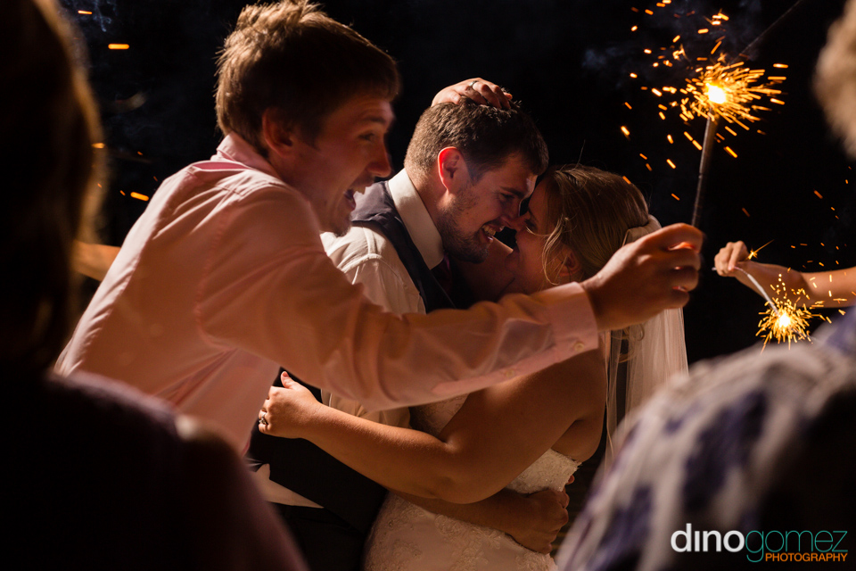 Sweet sparkler wedding photo of the bride and groom leaning in for a kiss by destination wedding photographer Dino Gomez