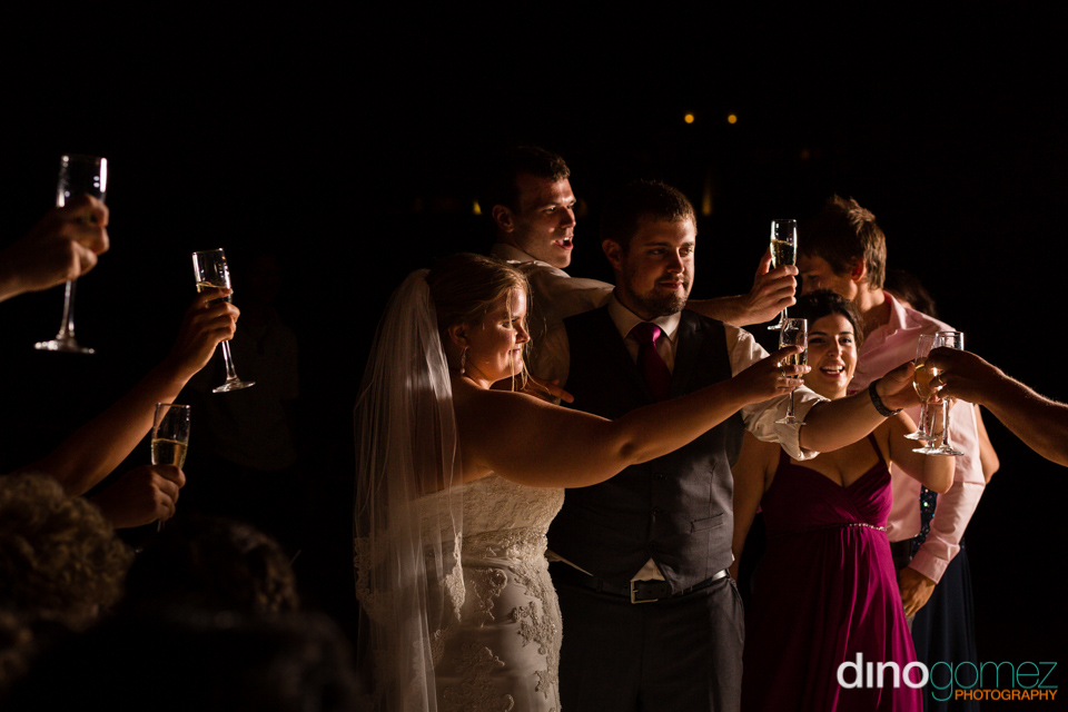 A nice shot of the newlyweds toasting while surrounded by friends at their Los Cabos destination wedding