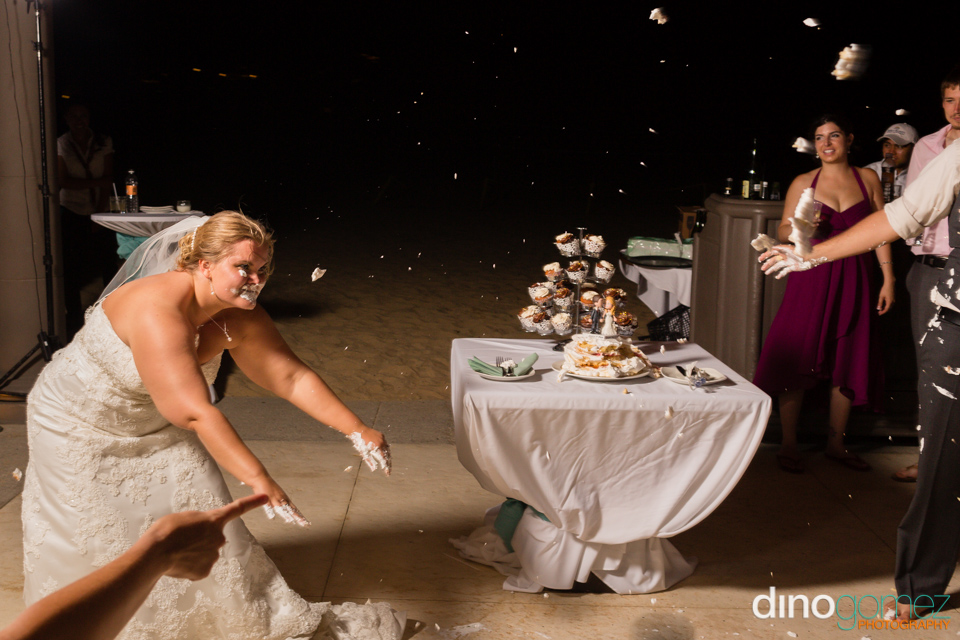 Bride throwing cake at her groom in Los Cabos at their destination wedding