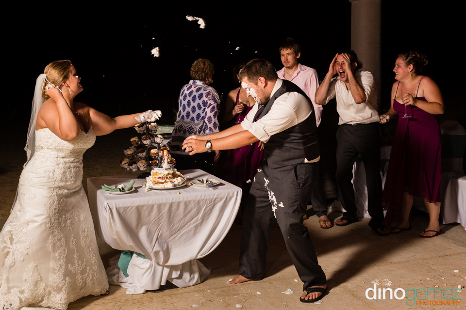 Newlyweds having fun and throwing cake at each other in Mexico