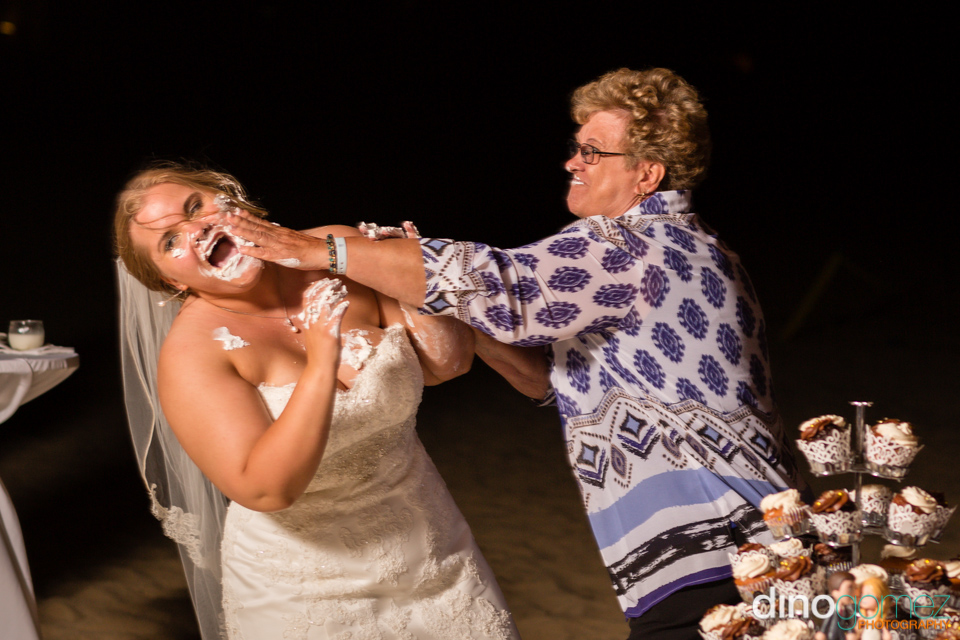 Cool shot of a woman rubbing cake on the bride's face in Mexico