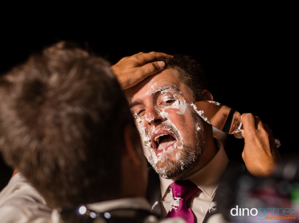 Man using a silver cake server to remove cake from the groom's face at his destination wedding