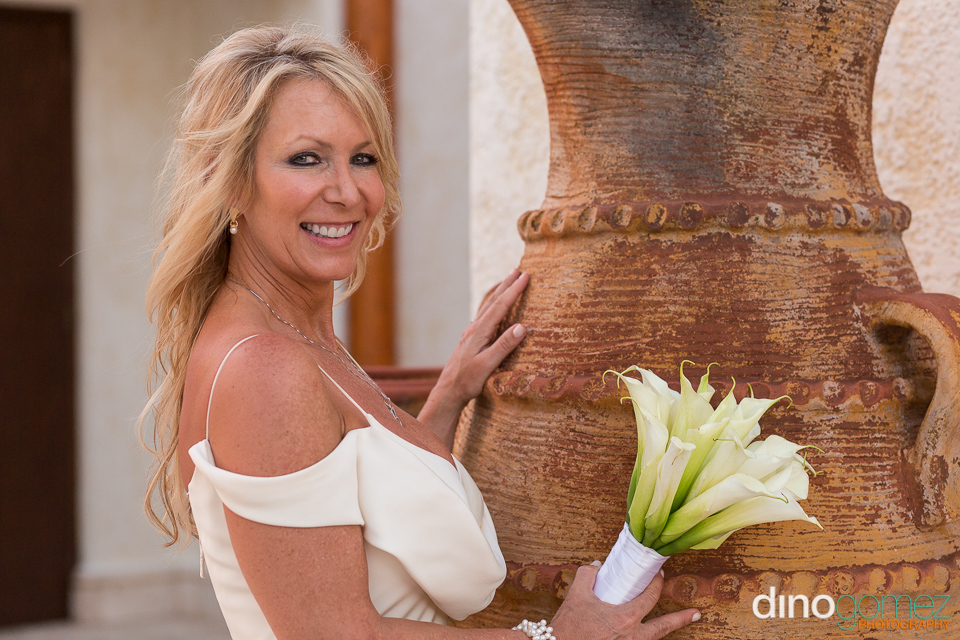 Beautiful blonde smiling on her anniversary in front of huge decorative planters pot